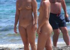 Sporty nude babes laughing together at the beach