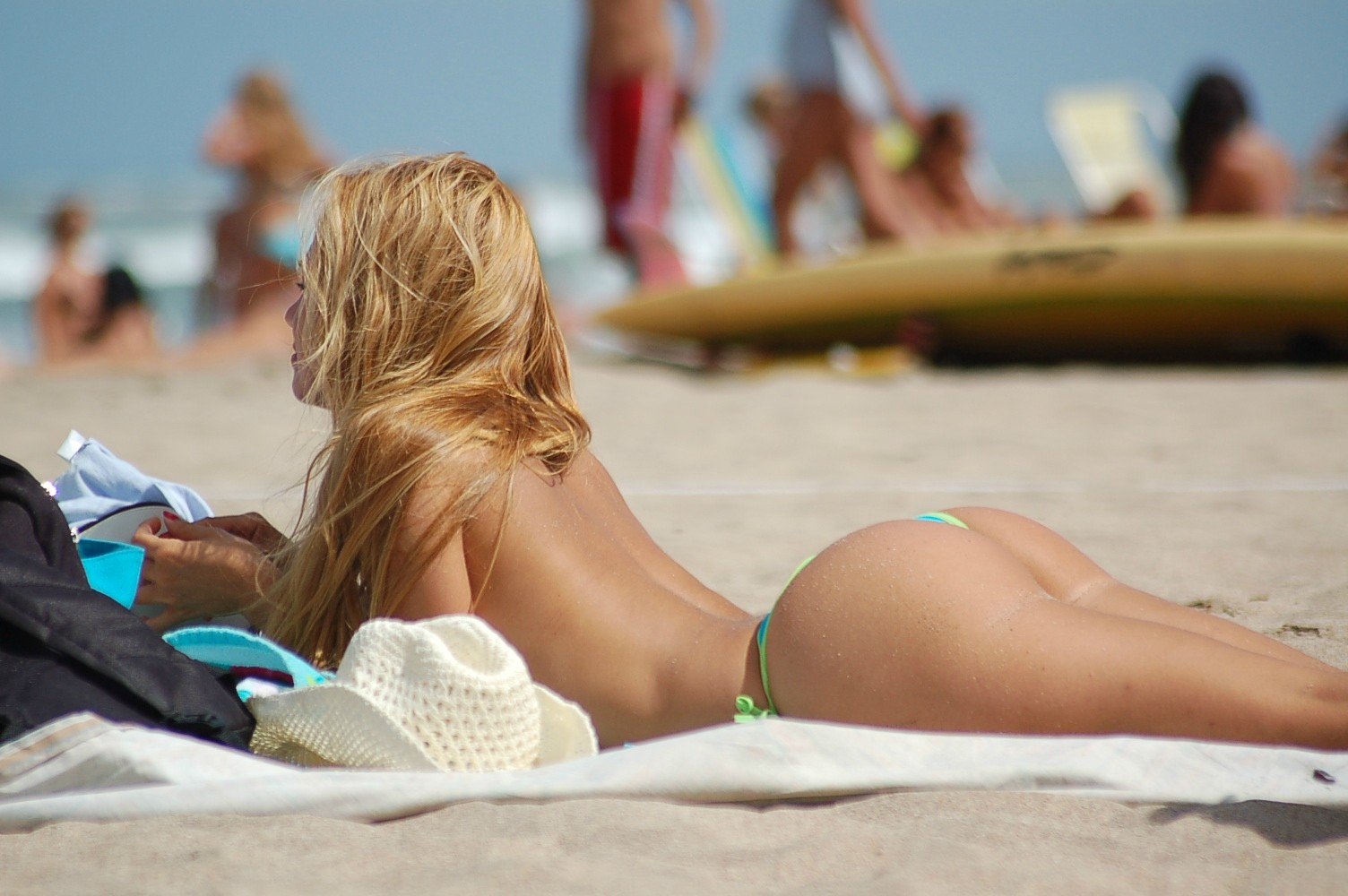 Hot blonde with an amazing ass reading on the beach