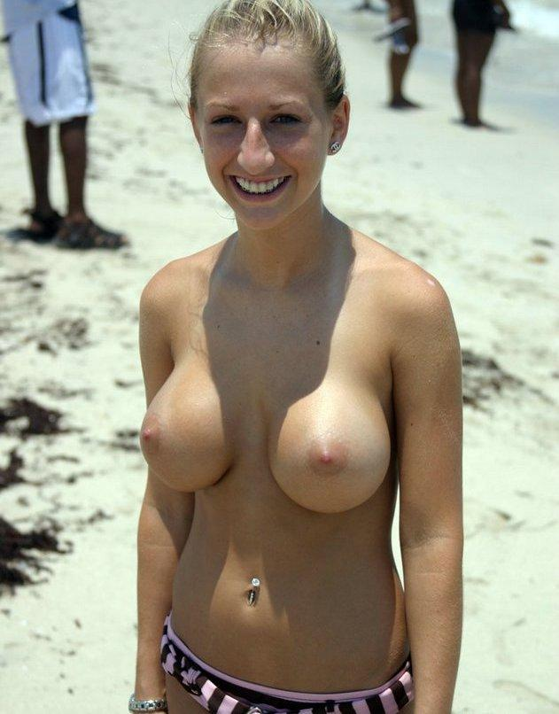 Blonde babe with big tits topless on a public beach