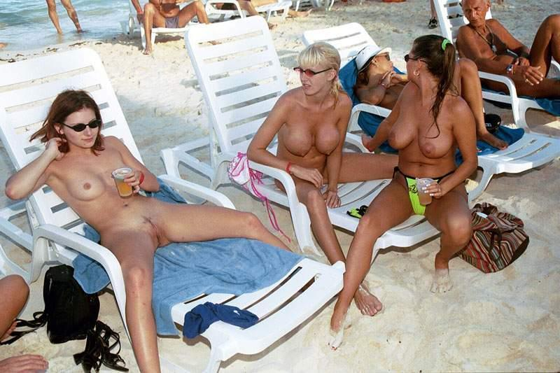 Large group of friends hanging out on the beach fully nude