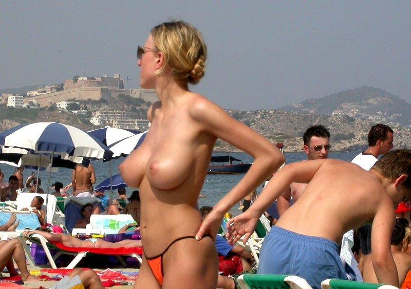 Blonde beach bimbo showing off her considerable assets