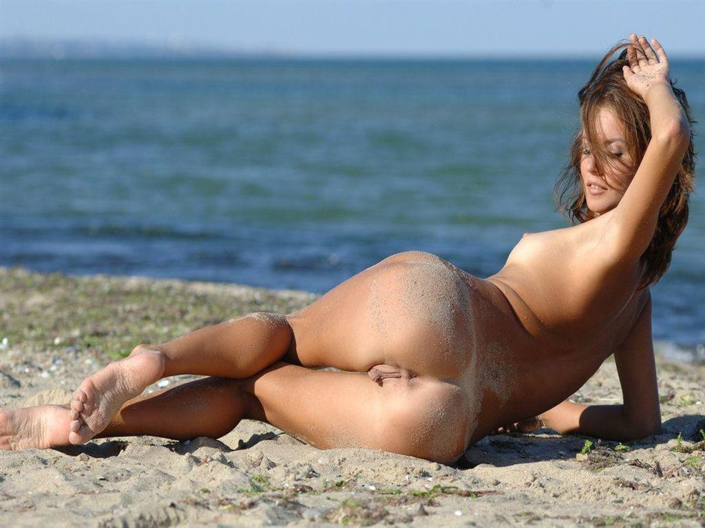 Sultry babe with bare pussy on the beach