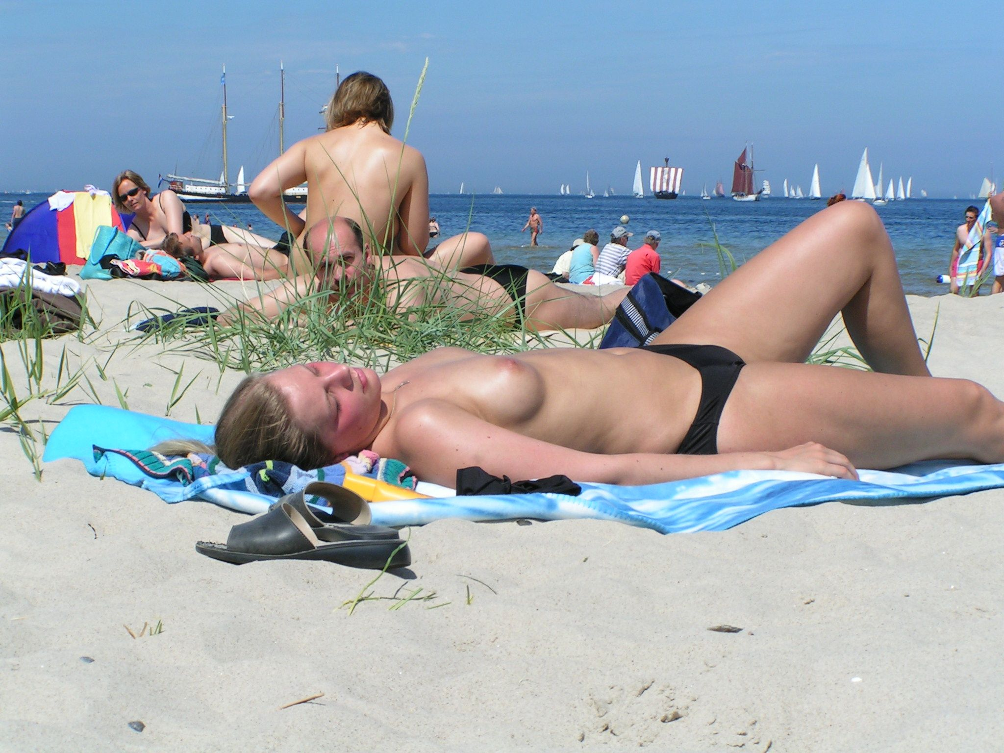 Blonde suntanning topless on a public beach