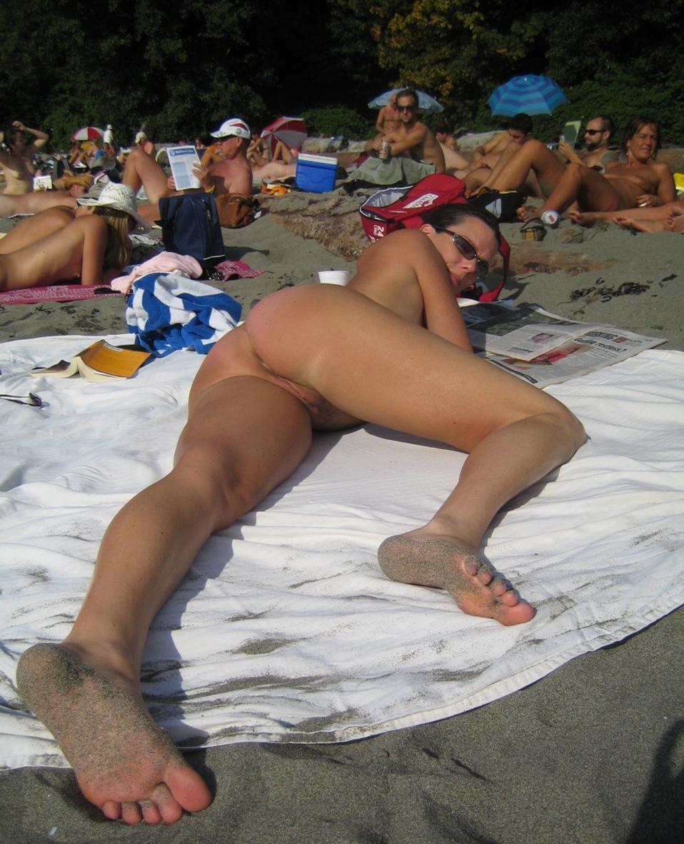 Naked brunette relaxing on the beach