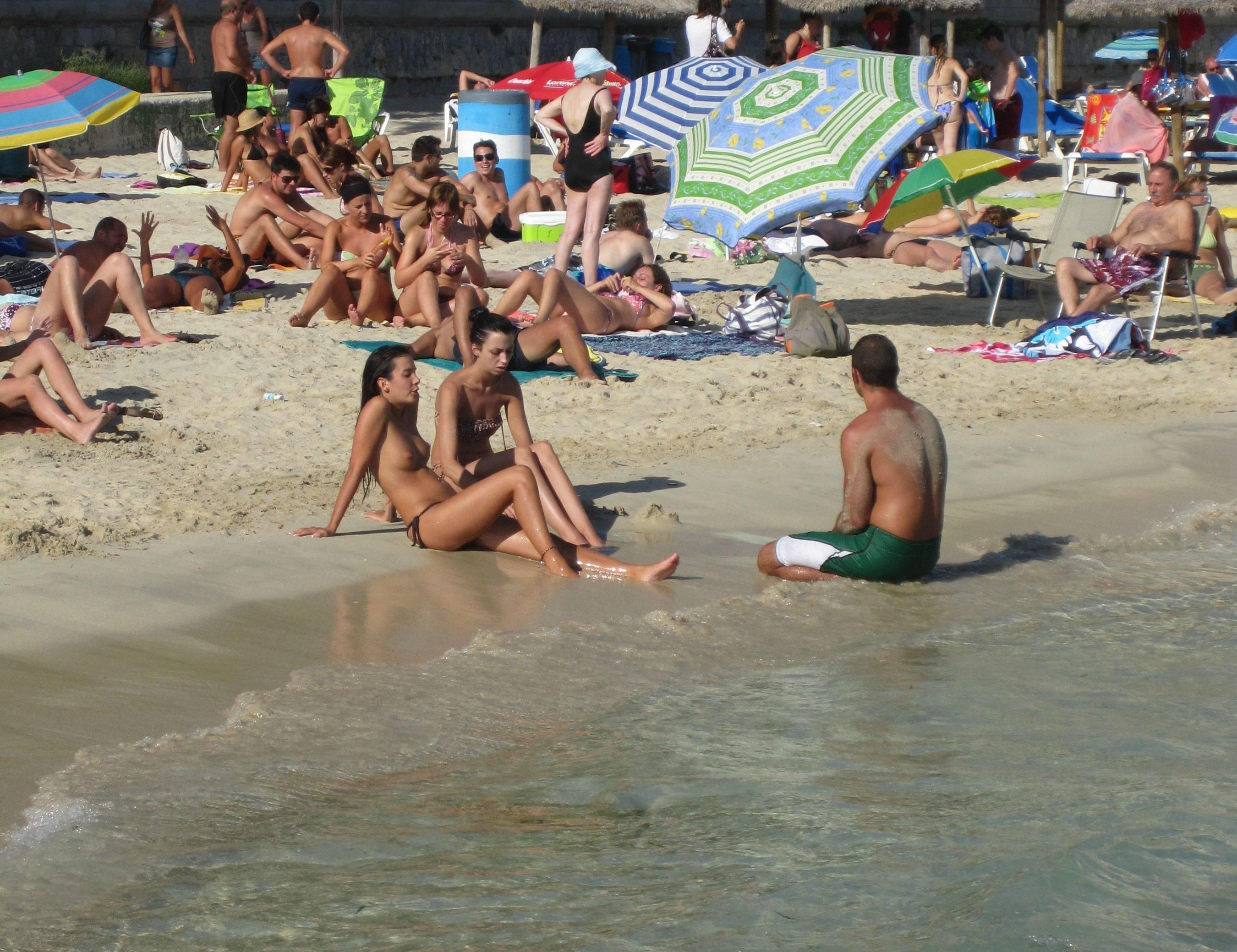 Topless teens feeling the surf on their feet