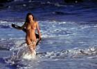 Nude brunette walking in the waves