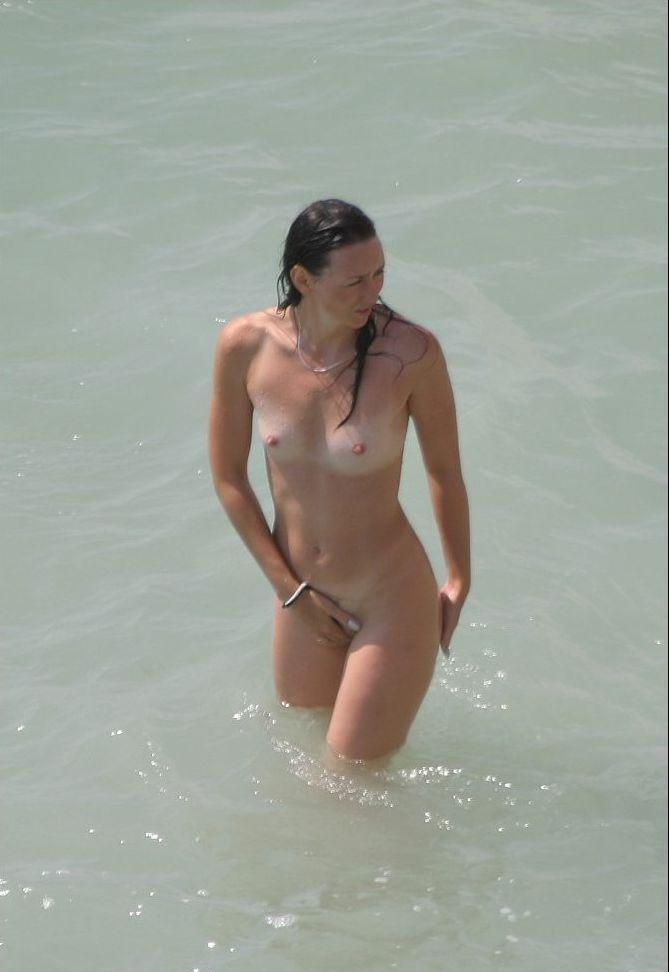 Nude babe in the warm water looks a bit shy
