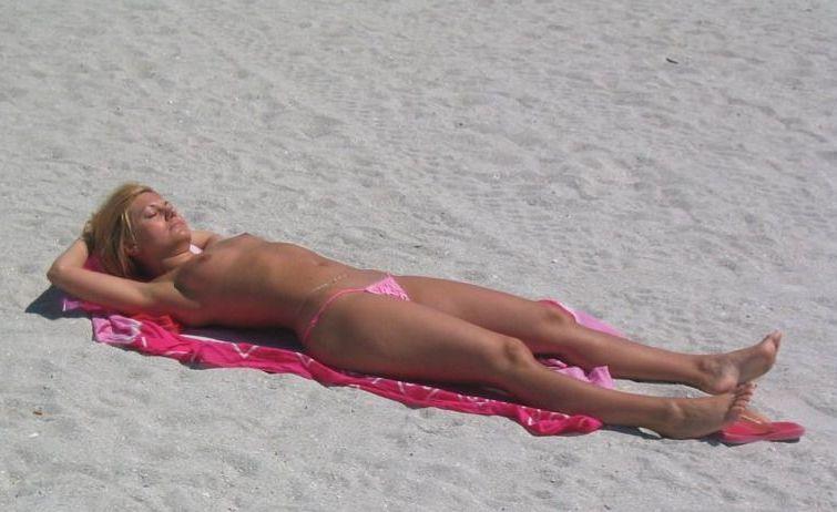 Sleeping beauty topless on the beach