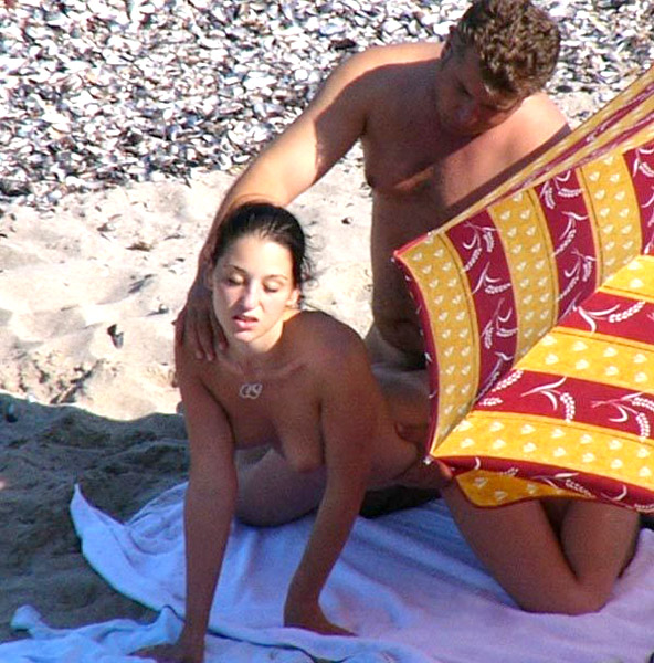 Couple caught in action on an empty beach