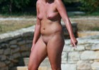 Confident nude blonde strolling outdoors naked