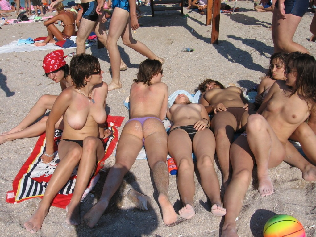 Group of hot naked friends relaxing on the beach