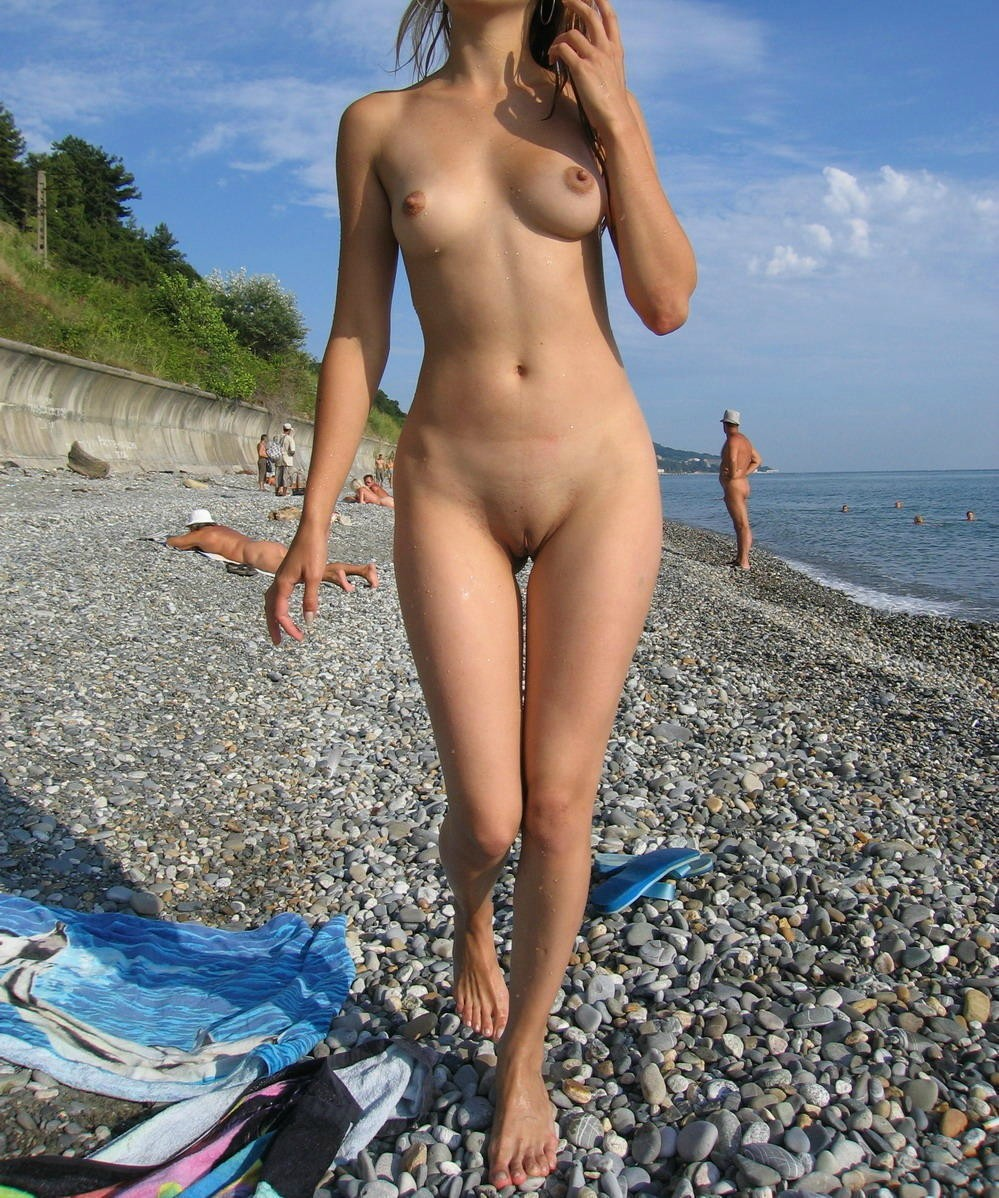 Nude hottie walking on rocky beach