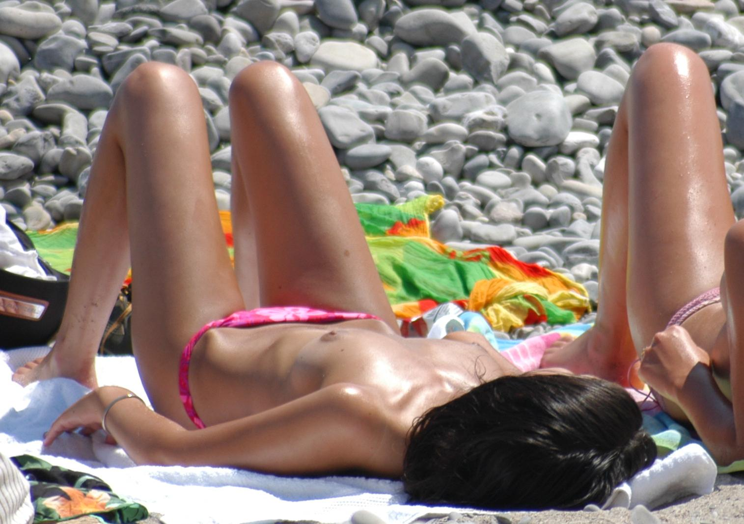 Skinny girl on beach oiled up and ready for fun