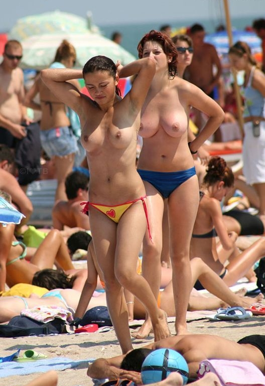 Topless babes out for a stroll on the beach