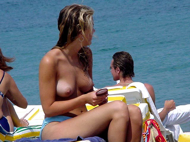 Topless beauty gets ready to rub lotion on that tan body