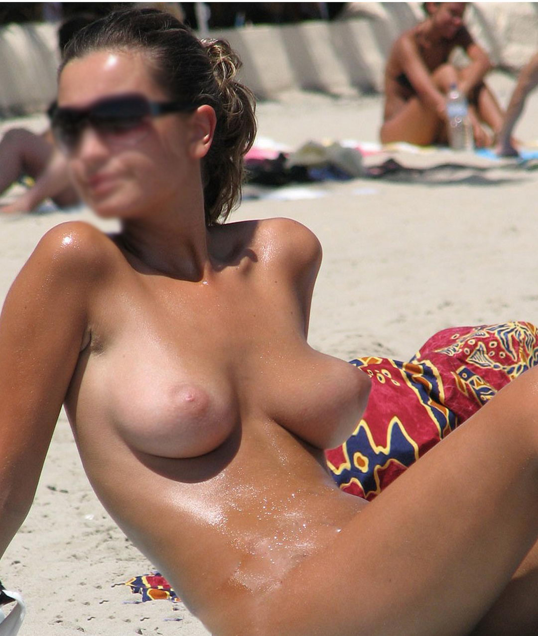Tanned woman shows off large tits on the beach