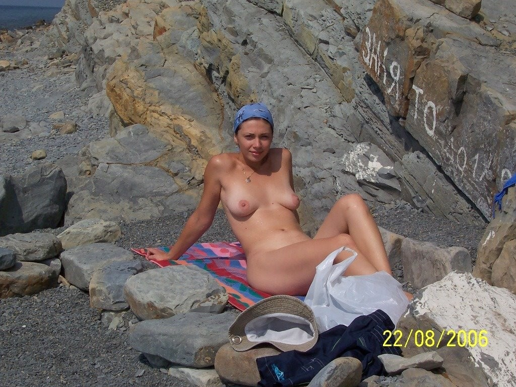 Nudist girl posing naked on rocky beach