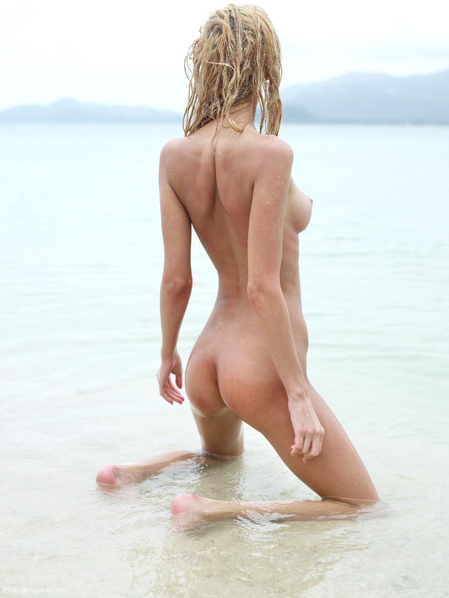 Nude girl posing on an exotic beach