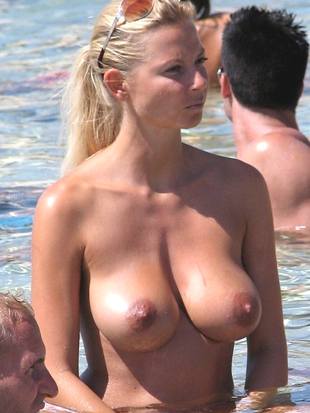 Woman with wet tits plays in the ocean