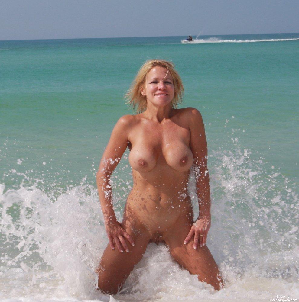 Flirty blonde splashing nude in the surf