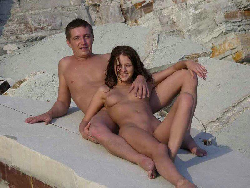Naked couple getting intimate on a public beach