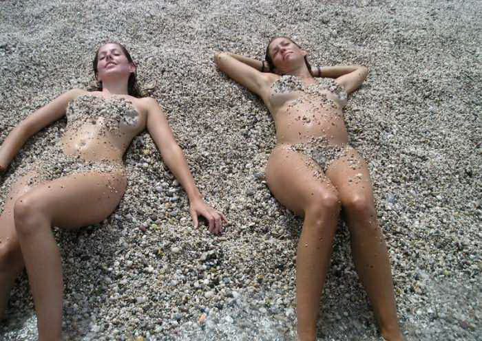 Nude beauties covered in sand