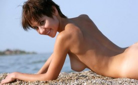 817-Pixie-haired-cutie-posing-topless-on-the-beach.jpg