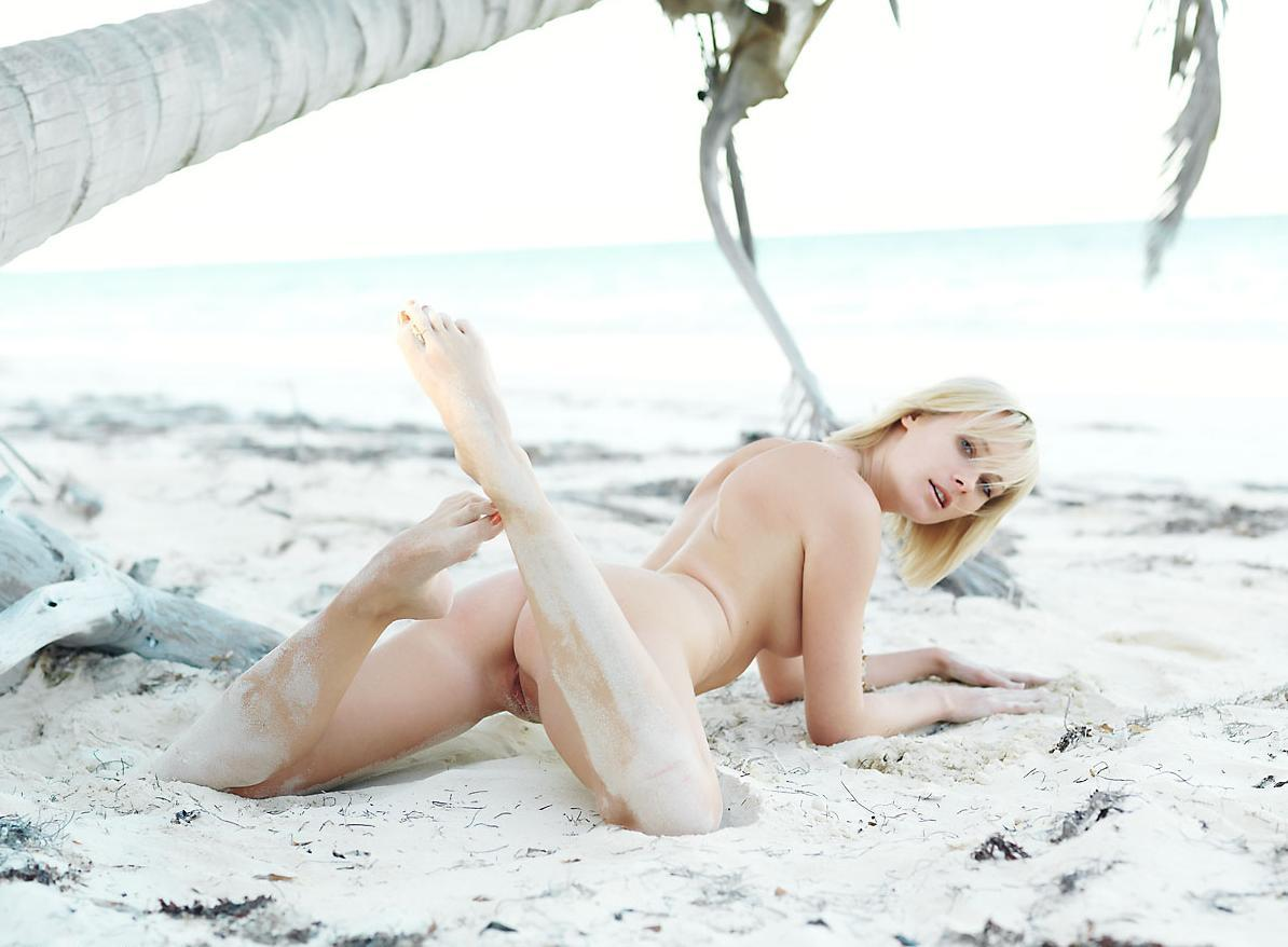 Sexy blonde showing her snatch in the sand