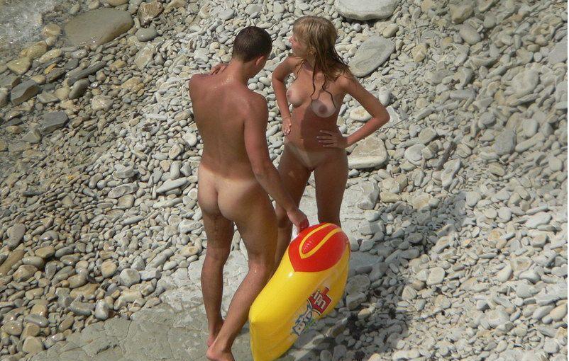 Nudist couple exposed on a rocky beach