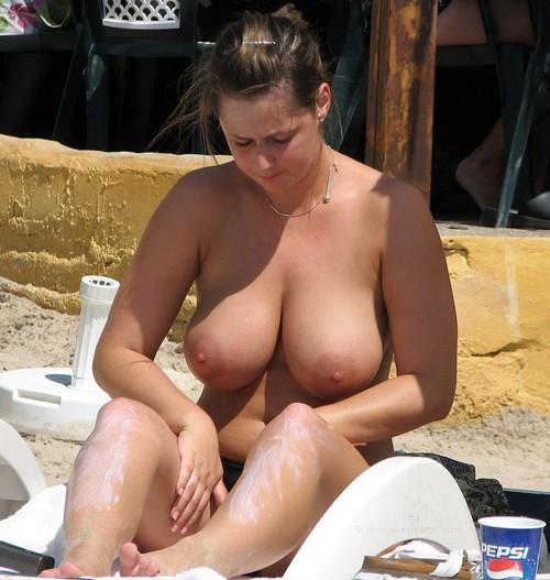 Topless babe applying suntan lotion on the beach