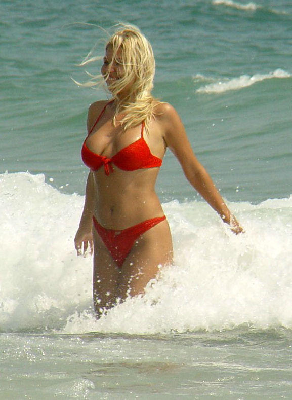 Hot voluptuous blond babe having fun in the waves
