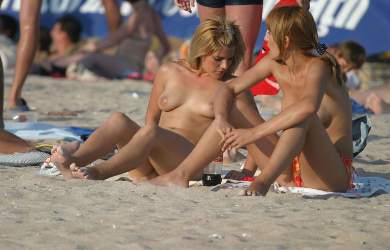 Mature sexy topless babes chatting at the beach