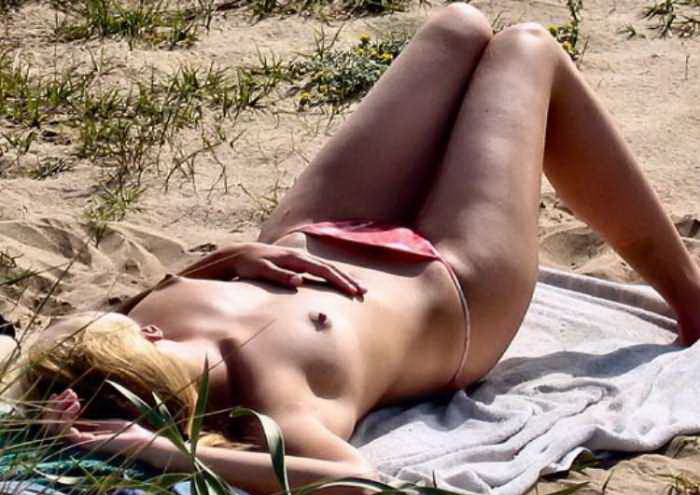 Skinny blonde napping topless in the sand