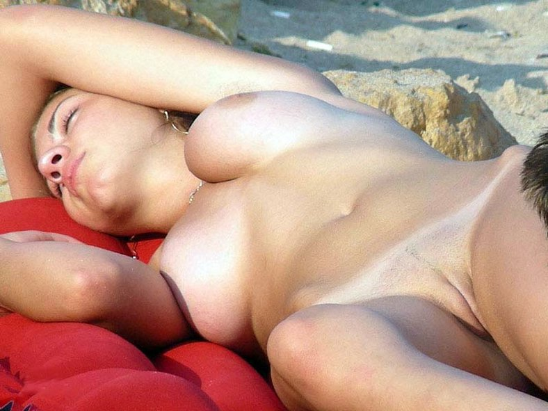 Hot babe napping nude on the beach