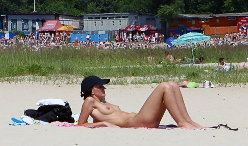 Naked wife tanning on the warm sand