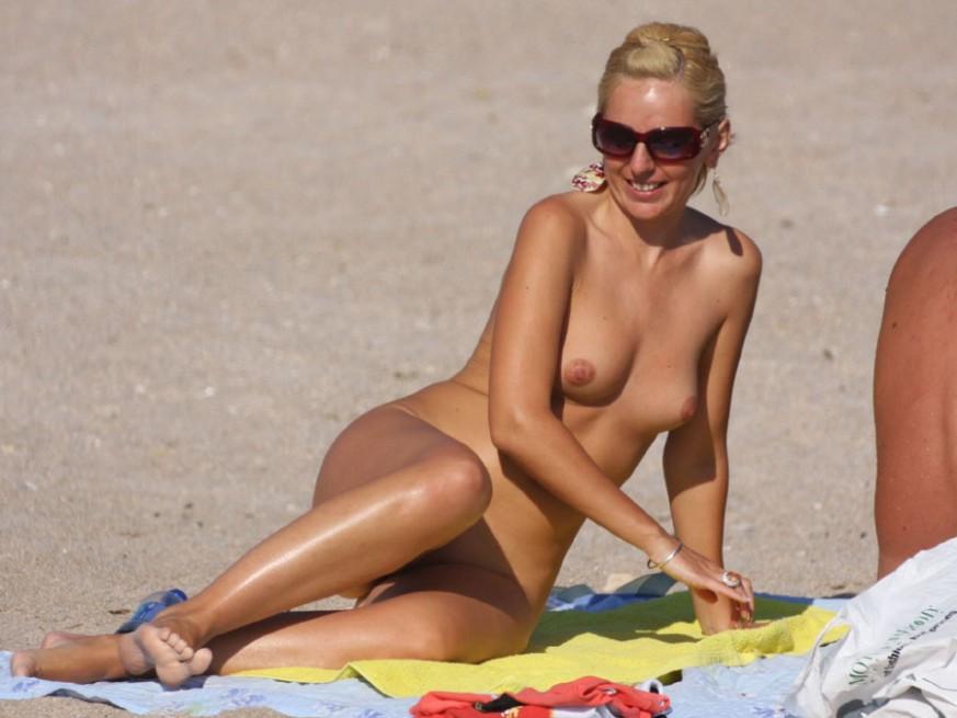 Smiling happy nude girl on nudist beach