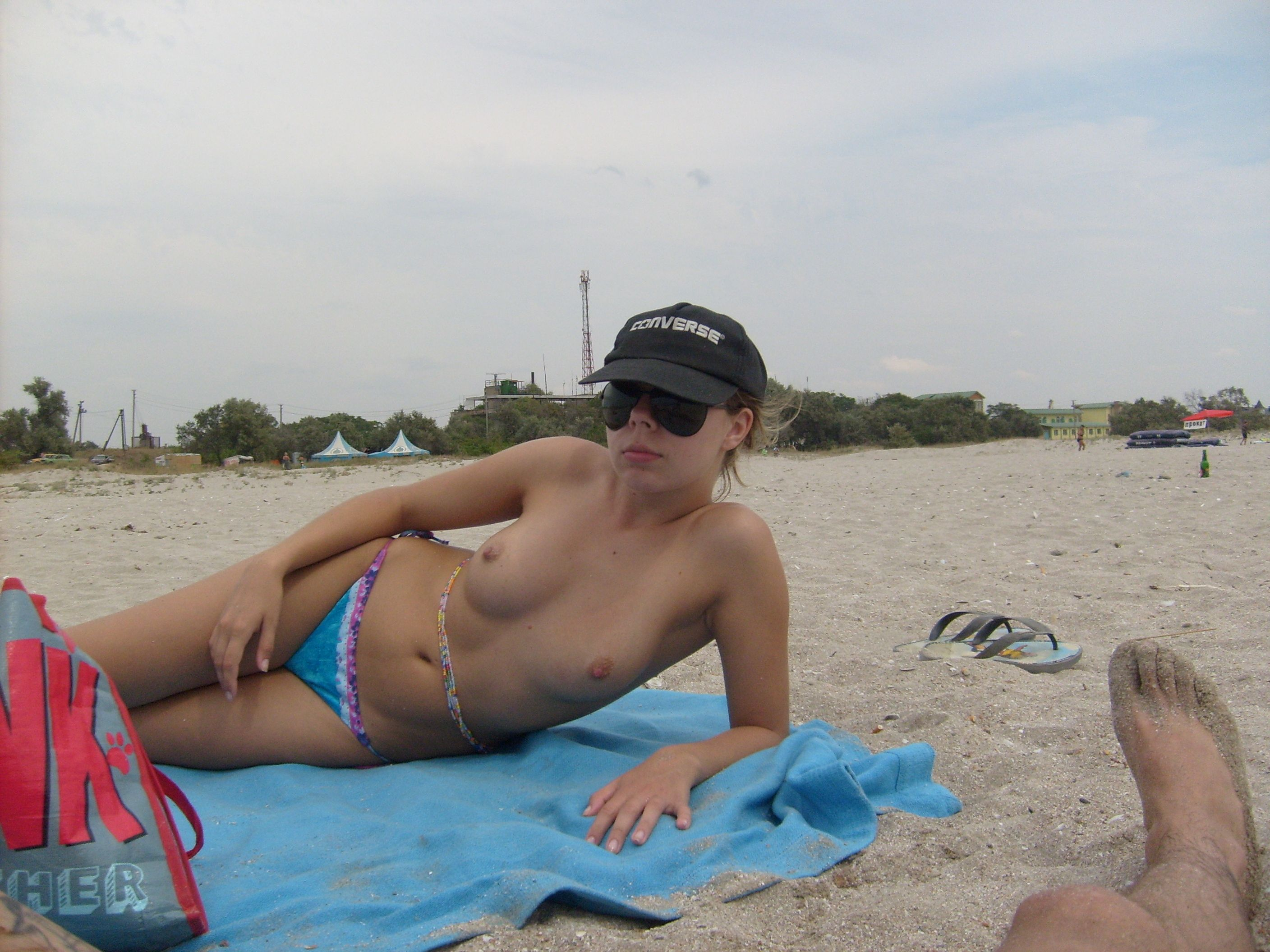 Fancy girlie sits topless for a hot tan