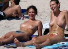 Hot topless chicks sharing a joke at the beach