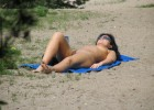 Naked woman enjoying the beach sun on her exposed body