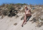 Nude blond diva laying on the warm sandy beach